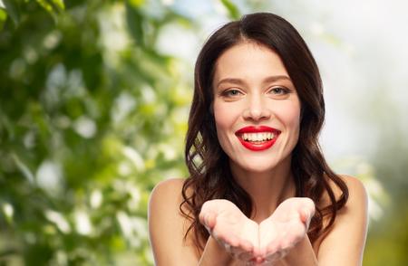 Schönheit, organisch, bilden und Leutekonzept - glückliche lächelnde junge Frau mit dem roten Lippenstift, der etwas eingebildet auf Palmen über grünem natürlichem Hintergrund hält Standard-Bild - 94242222