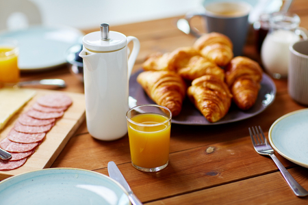 food and eating concept - coffee pot and glass of orange juice on served wooden table at breakfast