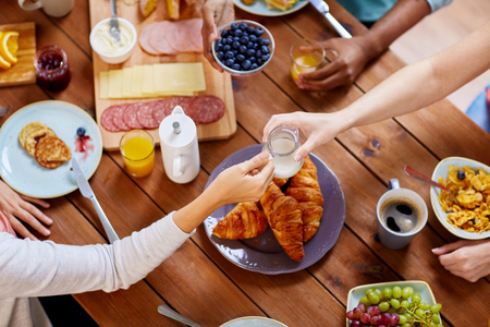 food, eating and family concept - group of people sharing milk or cream for breakfast at wooden table