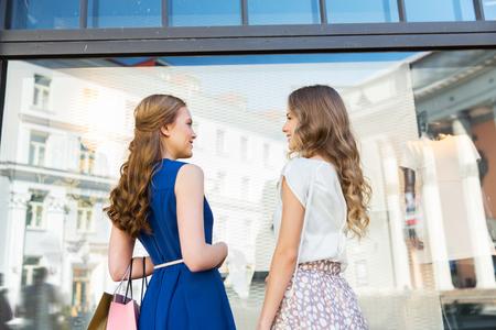 gelukkige vrouwen met boodschappentassen bij storefront Stockfoto