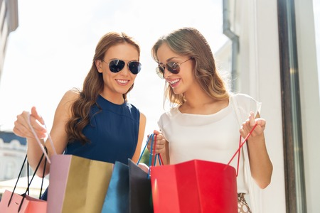 happy women looking into shopping bags outdoors