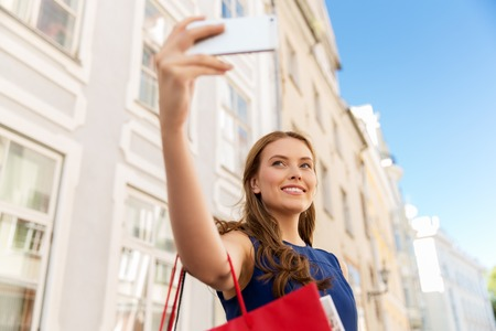 woman shopping and taking selfie by smartphone Stock Photo