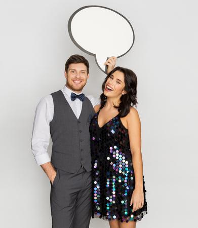 happy couple at party holding text bubble banner Foto de archivo