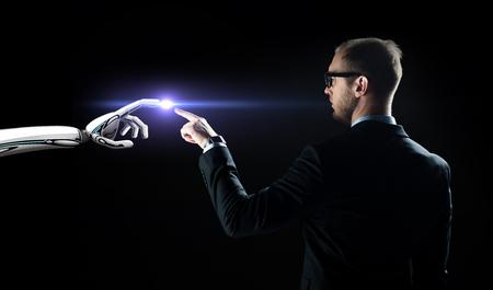 robot and human hand flash light over black Stock Photo