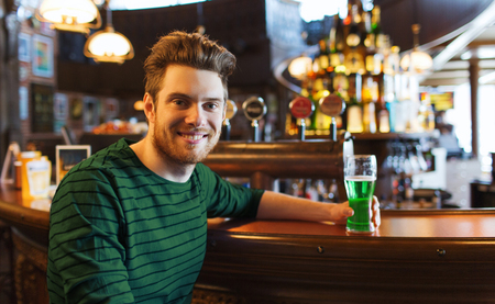 man drinking green beer at bar or pub Stock Photo - 94548854