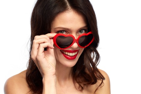 valentines day, beauty and people concept - close up of happy smiling young woman with red lipstick and heart shaped sunglasses over white background