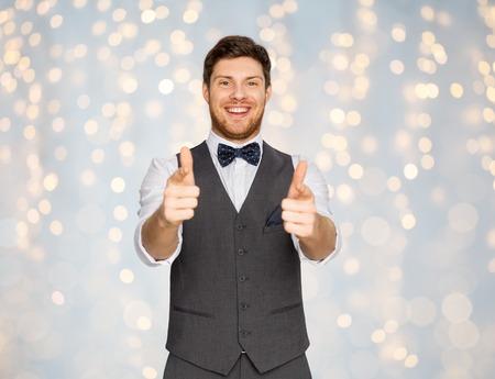 카메라를 가리키는 축제 양복에 행복 한 남자