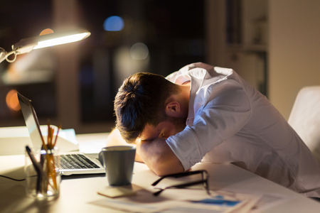 tired businessman lying on table at night office