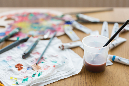 penseel inweken in kopje water op tafel Stockfoto