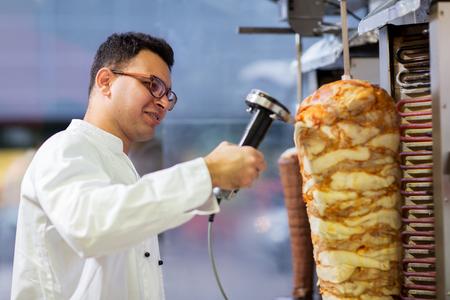 Chef che affetta la carne di doner dallo spiedo al negozio di kebab Archivio Fotografico - 94819005