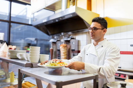 chef with dish on plate at kebab shop