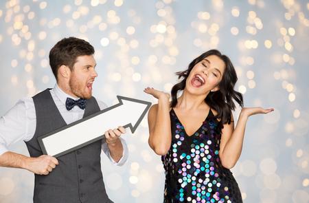 パーティーで大きな矢印を持つ幸せなカップル