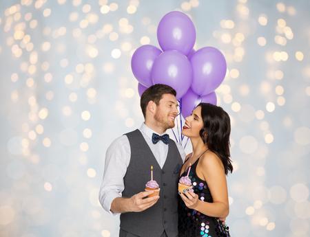 パーティーで風船とカップケーキを持つ幸せなカップル 写真素材