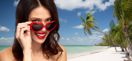 woman in heart shaped shades on summer beach Stock Photo