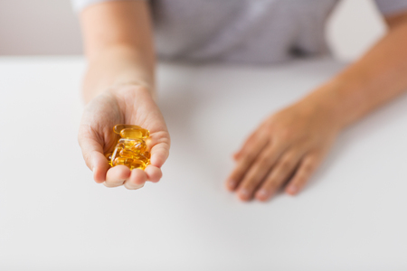 hand holding cod liver oil capsules