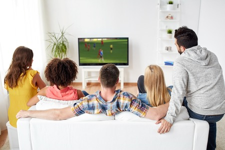 friends watching soccer game on tv at home