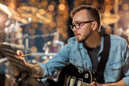 man met gitaar schrijven naar muziek boek in de studio