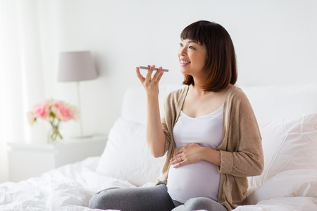 pregnant woman using voice recorder on smartphone