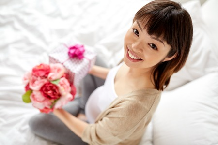 happy asian pregnant woman with gift and flowers Foto de archivo