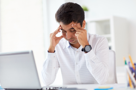 stressed businessman with laptop at office