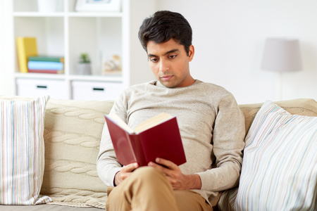 man sitting on sofa and reading book at home Stock Photo