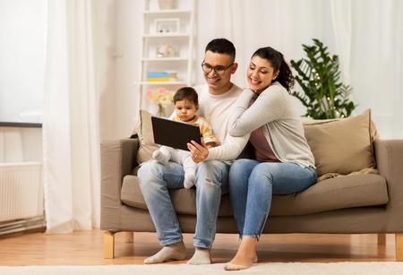 mère, père et bébé avec tablet pc à la maison