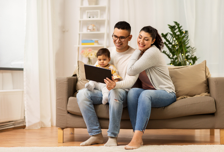 mother, father and baby with tablet pc at home