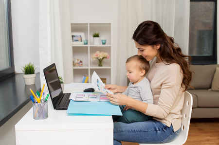 mother with baby and documents working at home