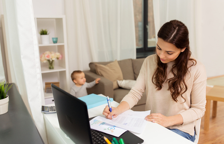 happy mother with baby and papers working at home Stockfoto