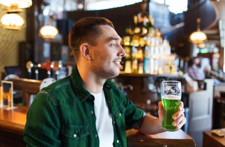man drinking green beer at bar or pub