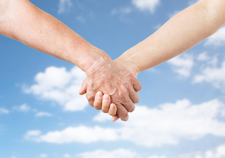 close up of senior and young woman holding hands