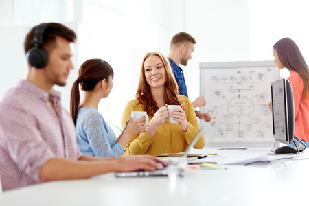 happy creative team drinking coffee at office Stock Photo