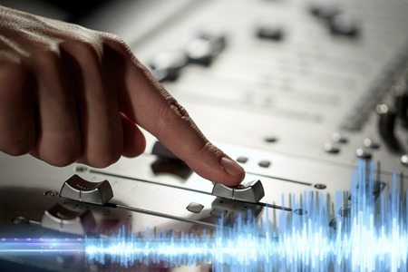 hand using mixing console for music recording Stock Photo
