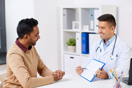 happy doctor and male patient meeting at hospital