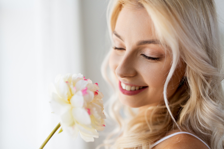 close up of beautiful young woman smelling flower