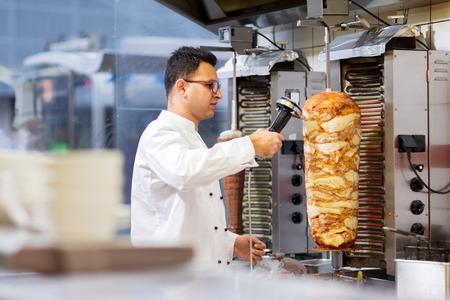 ケバブ店で唾を吐いてドナー肉をスライスするシェフ