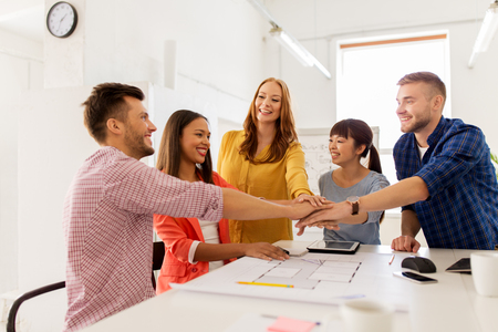 creative team holding hands together at office