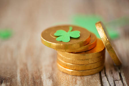 gold coins with shamrock on wooden table