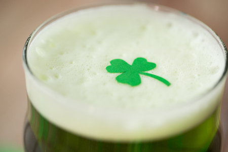 close up of glass of green beer with shamrock