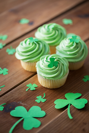 green cupcakes with shamrock decorations on table
