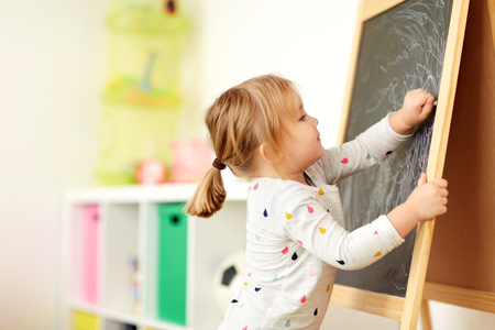 happy little girl drawing on chalk board at home