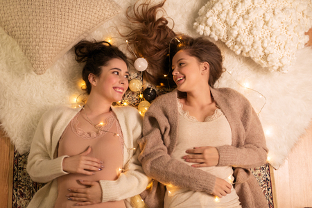 happy female friends in pajamas at home Stock Photo