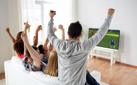 friends watching soccer on tv and celebrating goal