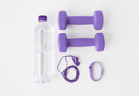 dumbbells, fitness tracker, earphones and bottle