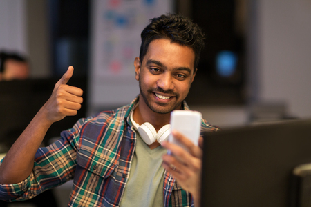 man with smartphone having video call at office Stock Photo