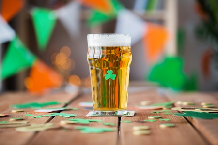 glass of beer, shamrock and coins on wooden table