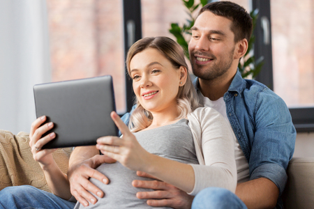 man and pregnant woman with tablet pc at home