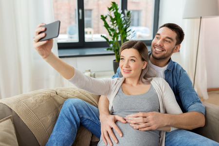 man and pregnant woman taking selfie at home