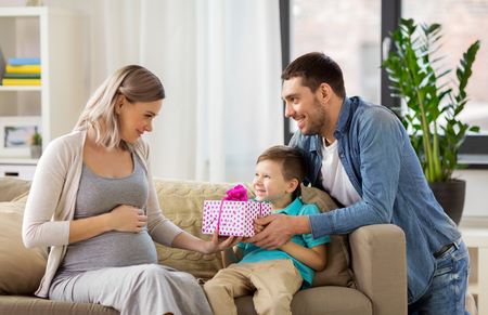 family giving present to pregnant mother at home