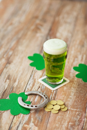 glass of green beer, horseshoe and gold coins